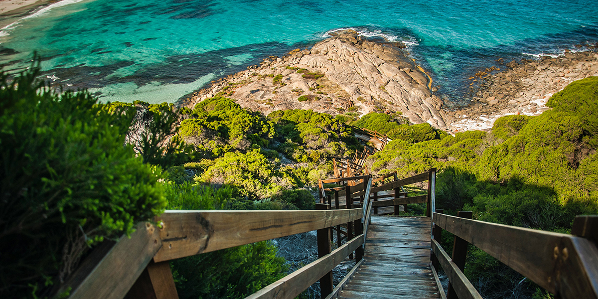 A view to a rocky beach down a timber staircase